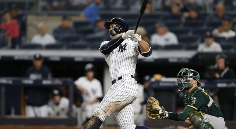 Yankees left fielder Giancarlo Stanton hits a solo home run during the eighth inning against the Oakland Athletics on Oct. 3, 2018, in a wild-card playoff game at Yankee Stadium.