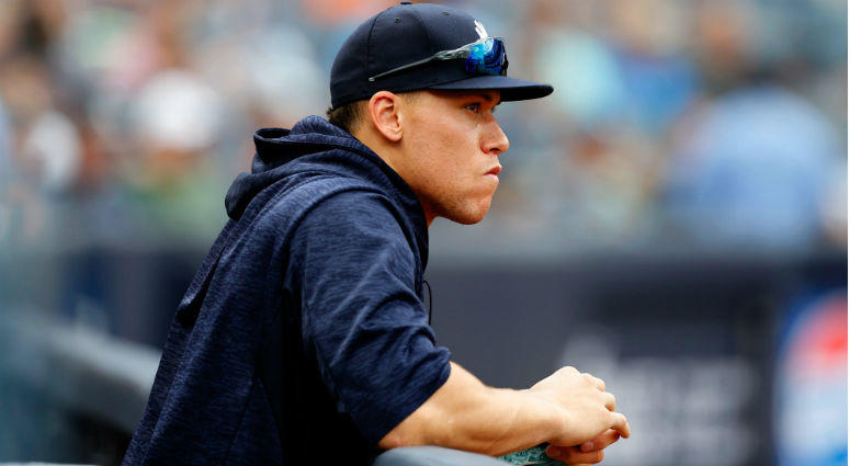 Aaron Judge watches game against Baltimore Orioles from dugout at Yankee Stadium.