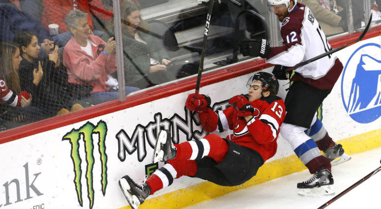 Nico Hischier goes down after a check by Patrik Nemeth during the third period at Prudential Center.