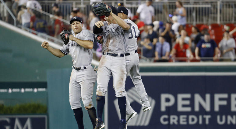 The Yankees' Giancarlo Stanton (left), Aaron Judge (center), and Aaron Hicks celebrate after their game against the Nationals on June 18, 2018, at Nationals Park in Washington, D.C.