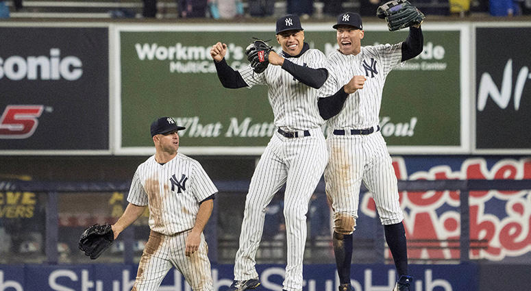 New York Yankees left fielder Giancarlo Stanton (27) and right fielder Aaron Judge (99) celebrate with left fielder Brett Gardner (11) after the ninth inning of the game against the Tampa Bay Rays at Yankee Stadium on Apr 3, 2018.