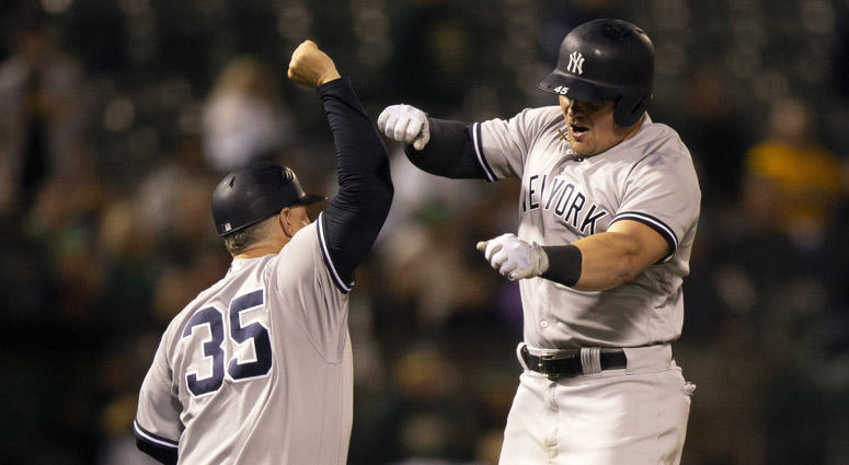 The Yankees' Luke Voit celebrates his solo home run with third-base coach Phil Nevin on Sept. 4, 2018, at Oakland Coliseum in Oakland, California.