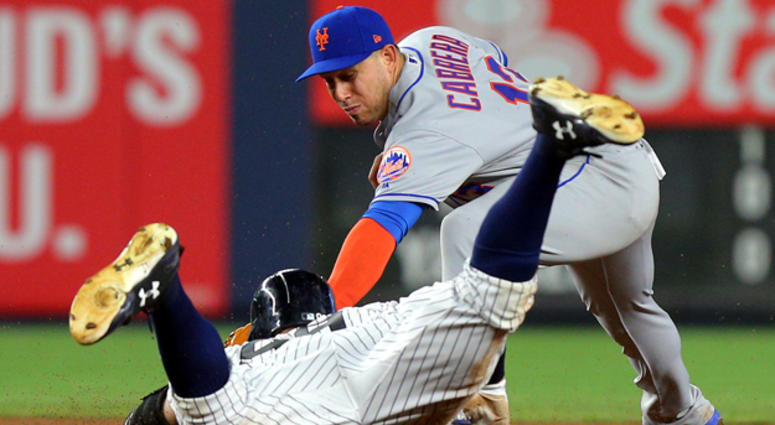 The Yankees' Aaron Judge (99) slides into second for a double ahead of a tag by Mets second baseman Asdrubal Cabrera on Aug. 15, 2017, at Yankee Stadium.