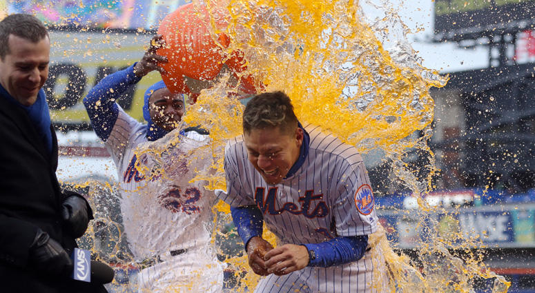 Mets first baseman Wilmer Flores is doused by Yoenis Cespedes during a postgame interview after hitting a walk-off solo home run against the Milwaukee Brewers on April 16, 2018, at Citi Field.