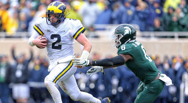 Michigan quarterback Shea Patterson runs though the tackle of Michigan State safety David Dowell on Oct. 20, 2018, at Spartan Stadium in East Lansing, Michigan.