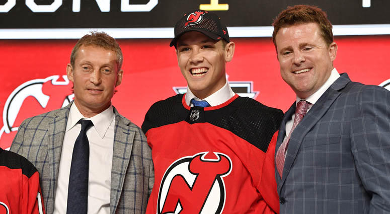 Ty Smith poses for a photo with team representatives after being selected as the 17th overall pick to the New Jersey Devils in the first round of the 2018 NHL Draft on June 22, 2018, at American Airlines Center in Dallas.