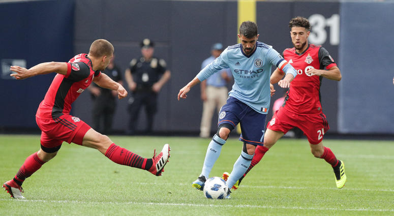 New York City forward David Villa controls the ball as Toronto FC midfielder Jonathan Osorio (21) and defender Nick Hagglund on Aug. 12, 2018, at Yankee Stadium.