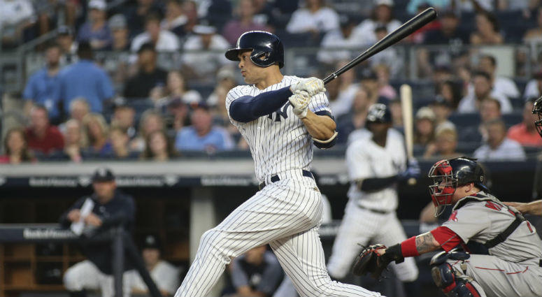 Yankees designated hitter Giancarlo Stanton hits a single against the Boston Red Sox on July 1, 2018, at Yankee Stadium.