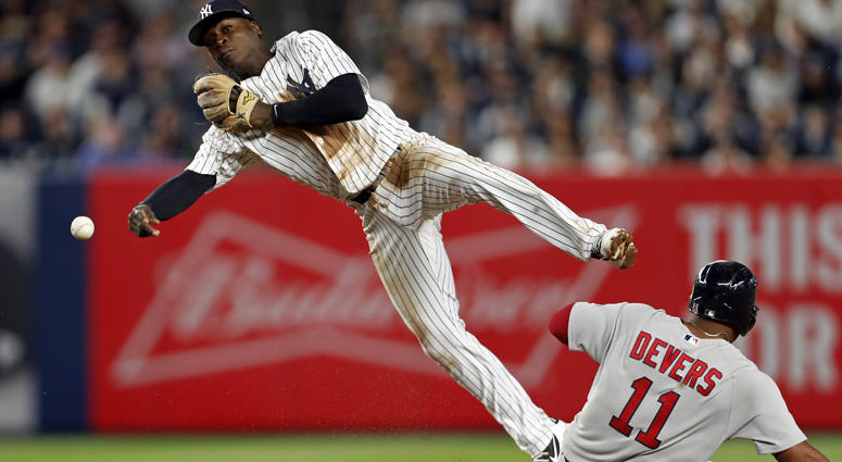 Yankees shortstop Didi Gregorius (18) turns the double play as the Red Sox's Rafael Devers slides into second base during the fourth inning at Yankee Stadium on May 9, 2018.