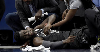 Brooklyn Nets guard Caris LeVert (22) is tended to after an injury during the second quarter of an NBA basketball game against the Minnesota Timberwolves on Nov. 12, 2018, in Minneapolis.