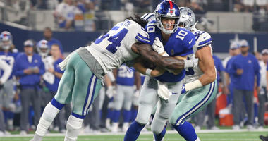 Eli Manning gets tackles on a run by Jaylon Smith at AT&T Stadium.