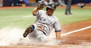 Yankees left fielder Brett Gardner slides home to score a run against the Tampa Bay Rays on July 25, 2018, at Tropicana Field in St. Petersburg, Florida.