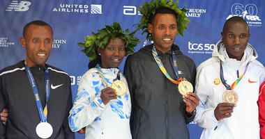 Nov 4, 2018; Lelisa Desisa of Ethiopia (center) and Mary Keitany of Kenya pose during the medal ceremony with Shura Kitata of Ethiopia (left) and Geoffrey Kamworor of Kenya (far right) after the New York City Marathon. Mandatory Credit: Vincent Carchietta
