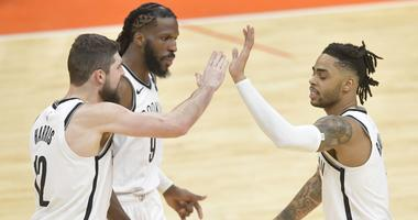 Nets guard D'Angelo Russell (right) celebrates with forward Joe Harris (left) and forward DeMarre Carroll in the third overtime against the Cleveland Cavaliers on Feb. 13, 2019, at Quicken Loans Arena.