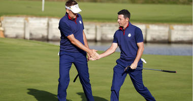 Europe golfer Ian Poulter and Europe golfer Rory McIlroy celebrate on the 15th green during the Ryder Cup Friday afternoon matches at Le Golf National.