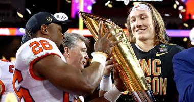 Clemson quarterback Trevor Lawrence, right, celebrates with the national championship trophy after beating Alabama during the College Football Playoff championship game on Jan. 7, 2019, at Levi's Stadium in Santa Clara, California.