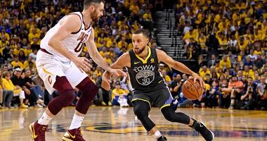 Warriors guard Stephen Curry drives to the basket against Cavaliers center Kevin Love during the fourth quarter in Game 2 of the NBA Finals on June 3, 2018, at Oracle Arena in Oakland, California.