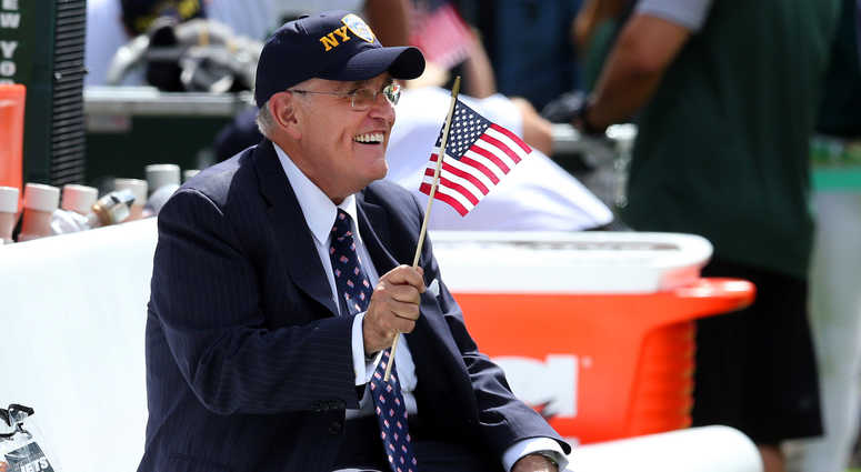 Sep 11, 2016; East Rutherford, NJ, USA; New York City former mayor Rudy Giuliani waves an American flag while sitting on the Jets bench before a game between the New York Jets and the Cincinnati Bengals at MetLife Stadium.