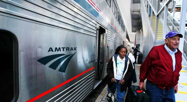 Passengers step off of an Amtrak train.