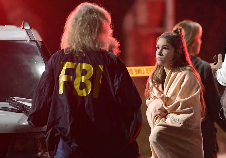 An FBI agent talks to a potential witness as they stand near the scene Thursday, Nov. 8, 2018, in Thousand Oaks, Calif. where a gunman opened fire.