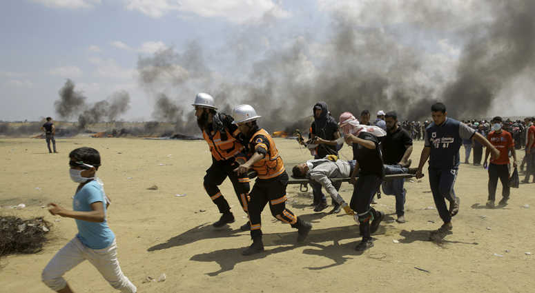 Palestinian medics and protesters evacuate a wounded youth during a protest at the Gaza Strip's border with Israel