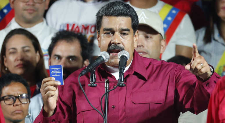 Venezuela's President Nicolas Maduro places his fist against his heart as he arrives with his wife Cilia Flores to address supporters from the presidential palace.