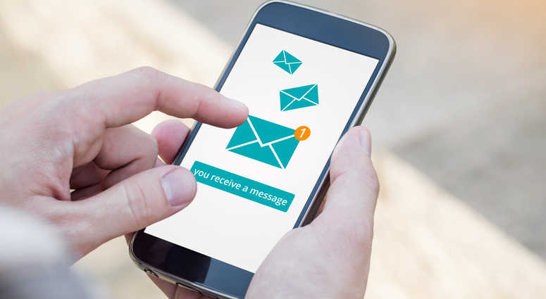 Email app on smartphone screen. You receive a message, New message is received. Man's Hand holding a smartphone