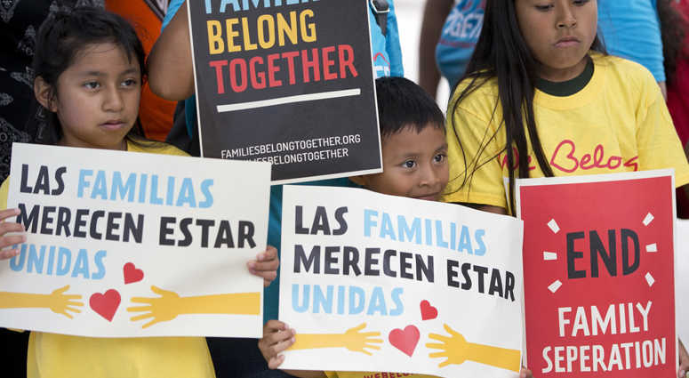 FILE - In this June 1, 2018, file photo, children hold signs during a demonstration in front of the Immigration and Customs Enforcement offices in Miramar, Fla.