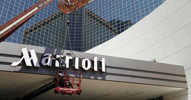 FILE - In this Tuesday, April 30, 2013, file photo, a man works on a new Marriott sign in front of the former Peabody Hotel in Little Rock, Ark.