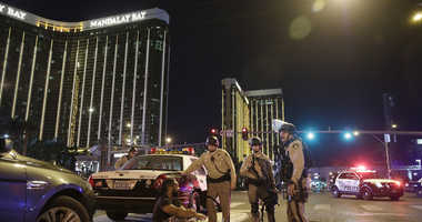 In this Oct. 1, 2017 file photo, police officers stand at the scene of a mass shooting near the Mandalay Bay resort and casino on the Las Vegas Strip