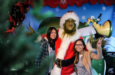 """A figure of """"Grinch"""" poses for photos with tourists during the """"Grinchmas"""" celebration at the Universal Studios Hollywood"""