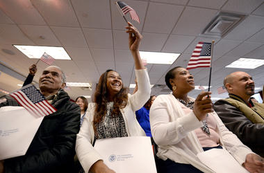 "Eusebio Concepcion de Jenkins waives an american flag ceremonial playing of ""America the Beautiful"" during Naturalization Ceremony for new US Citizens at the offices of U.S. Citizenship and Immigration Services in New York, NY, on January 13, 2017"