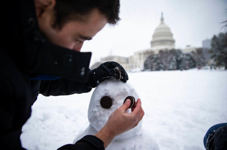 WASHINGTON, DC - JANUARY 13: Ivan Lopez, from Columbia, MD, uses Oreos to make eyes for his snowman, on the west side of the U.S. Capitol, on January 13, 2019 in Washington, DC.