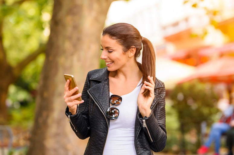 a woman looks at a smartphone