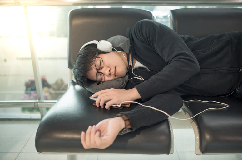 man asleep on a suitcase at the airport