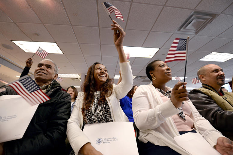 """Eusebio Concepcion de Jenkins waives an american flag ceremonial playing of """"America the Beautiful"""" during Naturalization Ceremony for new US Citizens at the offices of U.S. Citizenship and Immigration Services in New York, NY, on January 13, 2017"""