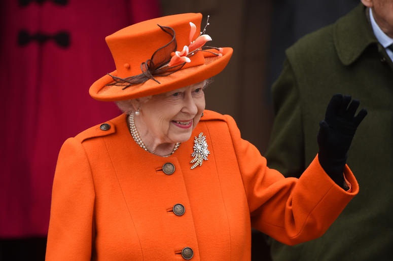 Queen Elizabeth II waves in an orange suit