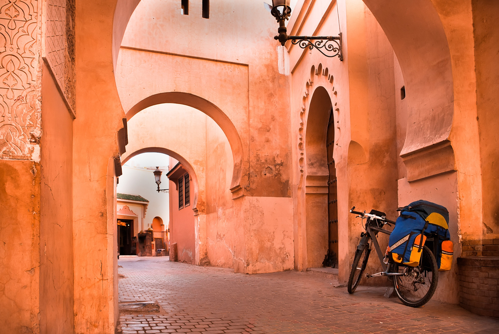 mountain bike standing near a red wall in the Muslim city of Marrakech in the street with beautiful arches and walls_184584899