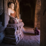 Neophyte praying with candle light in a Buddhist temple_406877149
