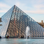 View of famous Louvre Museum with fountains in courtyard of Louvre Palace_392708875