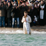 Orthodox priest blesses the sea water_364332482