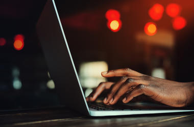 hands typing at laptop computer