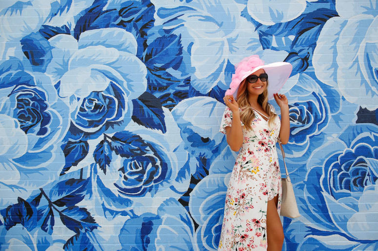 LOUISVILLE, KY - MAY 03: A woman adjusts her hat in front of a wall of painted roses ahead of the 144th Kentucky Derby at Churchill Downs on May 3, 2018 in Louisville, Kentucky.