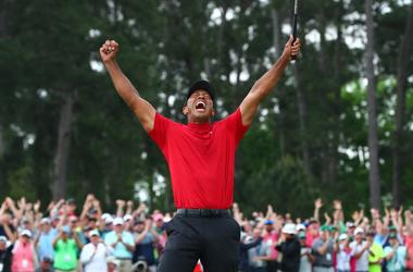 Tiger Woods celebrates after making a putt on the 18th green to win The Masters golf tournament at Augusta National Golf Club.
