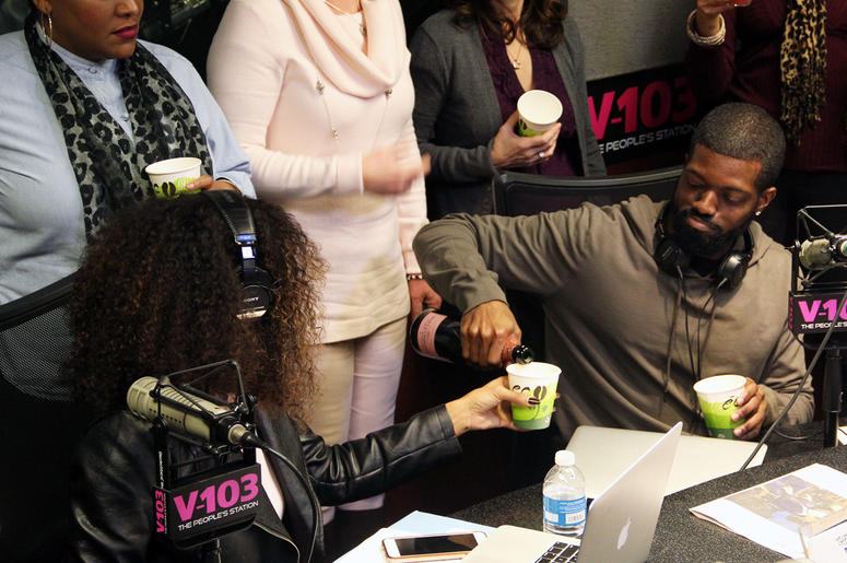 JR of The Morning Culture pouring Moet Champagne for co-host Jade Novah