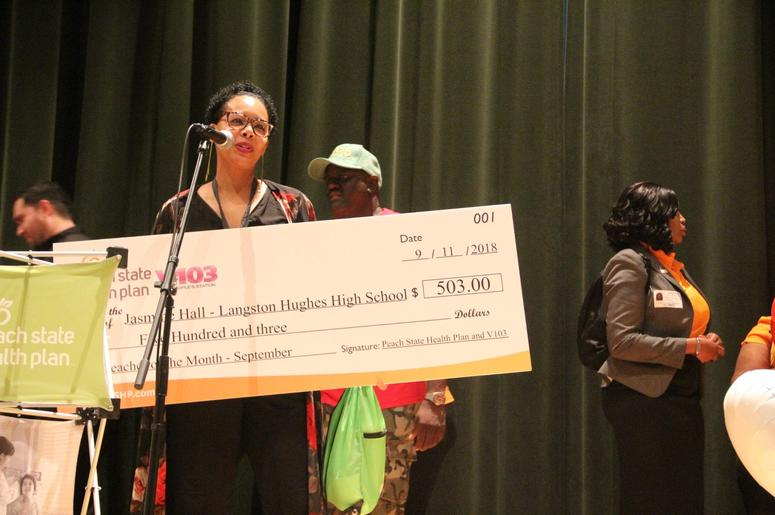 Jasmine Hall receives her Teacher of the Month award check