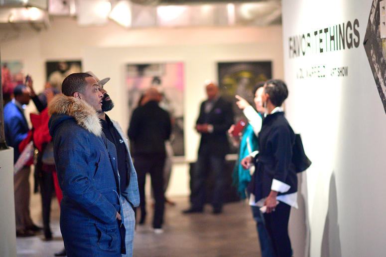 """T.I. and Trap Music Museum curator D.L. Warfield look at Warfield's art during his """"My Favorite Things"""" art exhibit on November 30, 2018, in Atlanta."""