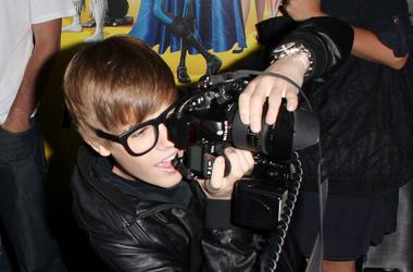 Justin Bieber shoots with a photographer's camera as he arrives to the premiere of 'Megamind 3D' in Hollywood, California