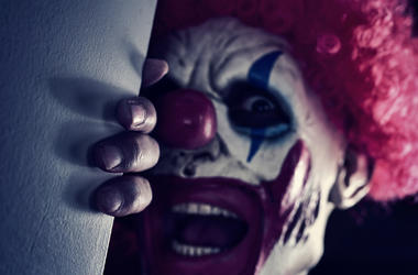 Closeup of a scary evil clown wearing a red hair wig, peering out from the corner