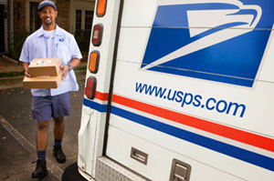 stock image of a united states postal worker carrying boxes to his truck